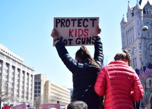 "girl on someone's shoulders at a rally with a sign that says ""protect kids not guns"""